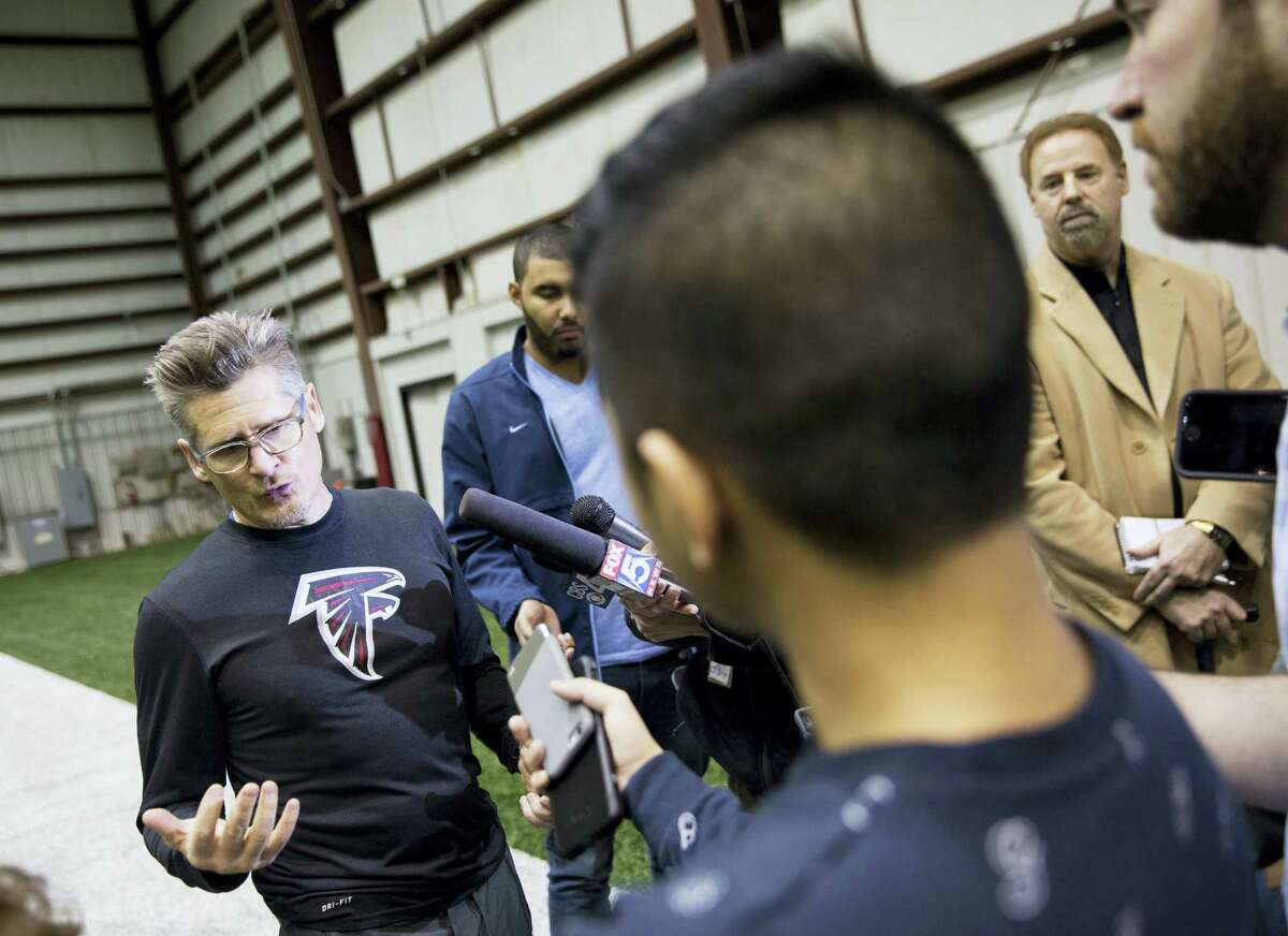 Atlanta Falcons general manager Thomas Dimitroff, left, answers questions from the media.