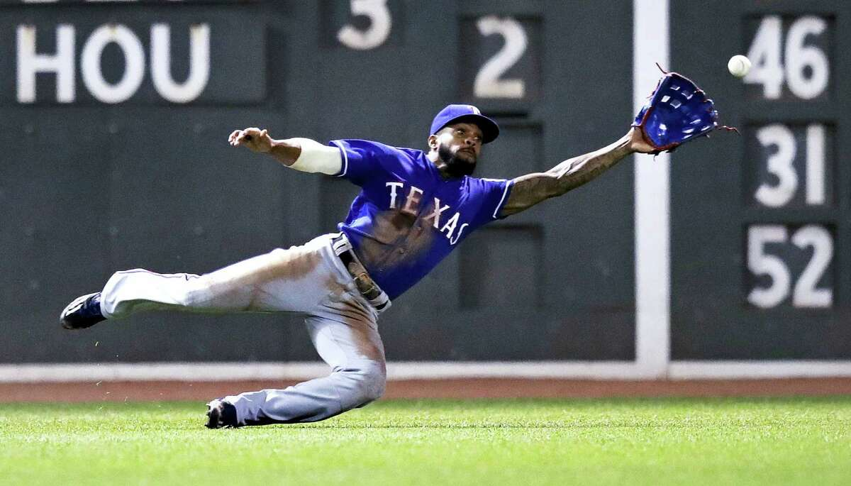 Texas Rangers left fielder Delino DeShields dives but can't make the play on an RBI double by Xander Bogaerts during the sixth inning of a baseball game at Fenway Park in Boston, Tuesday. The Red Sox won 11-6.