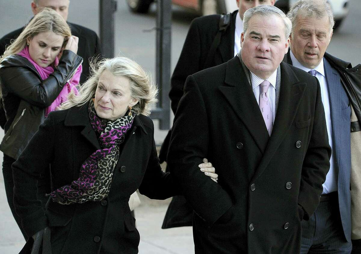 In this March 18, 2015 photo, former Connecticut Gov. John Rowland, right, and his wife, Patty, arrive at federal court in New Haven, Conn. The U.S. Supreme Court has declined to hear Rowland's appeal of his convictions for conspiring to hide his work on two congressional campaigns after having gone to prison for corruption.