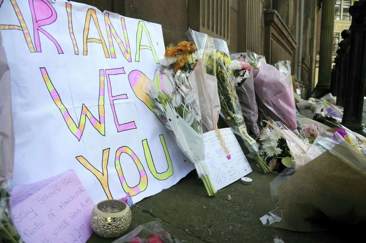 Flower tributes at St Ann's square, Manchester, England Tuesday May 23, 2017. The Islamic State group claimed responsibility Tuesday for the suicide attack at an Ariana Grande show that left more than 20 people dead as young concertgoers fled, some still wearing the American pop star's trademark kitten ears and holding pink balloons.
