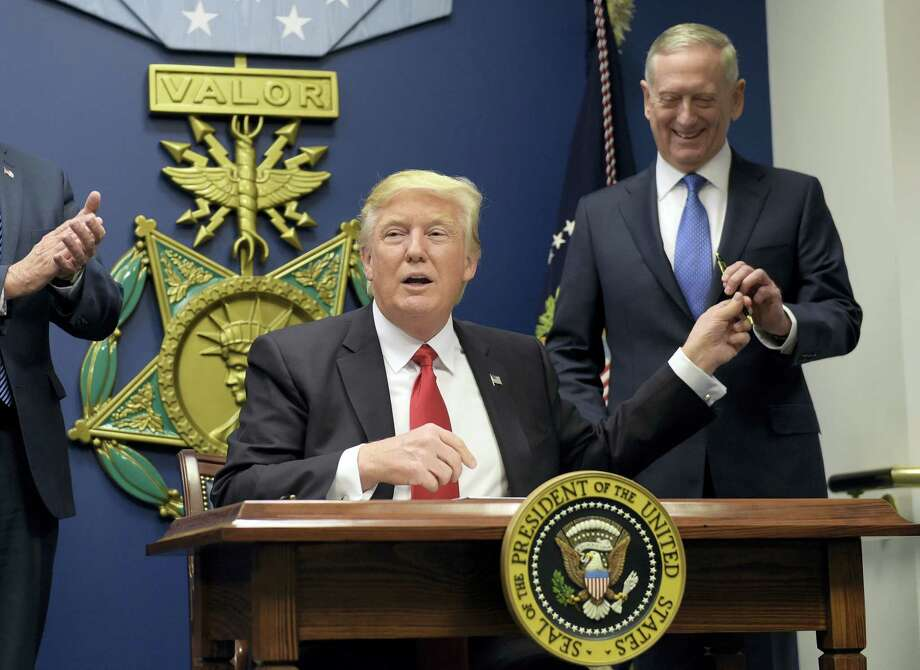 President Donald Trump, left, hands Defense Secretary James Mattis, right, a pen after he signed an executive action on rebuilding the military during an event at the Pentagon in Washington Friday. Photo: Susan Walsh — The Associated Press  / Copyright 2017 The Associated Press. All rights reserved.