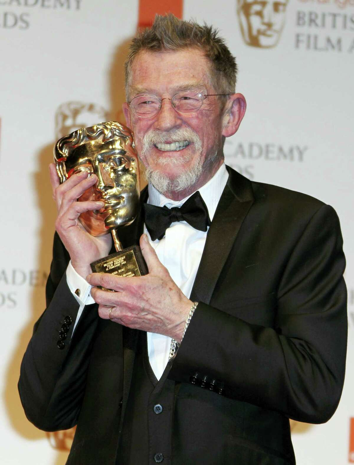 """Actor Sir John Hurt posing with his award for """"Outstanding Contribution to Cinema"""" backstage at the BAFTA Film Awards 2012, at The Royal Opera House in London."""