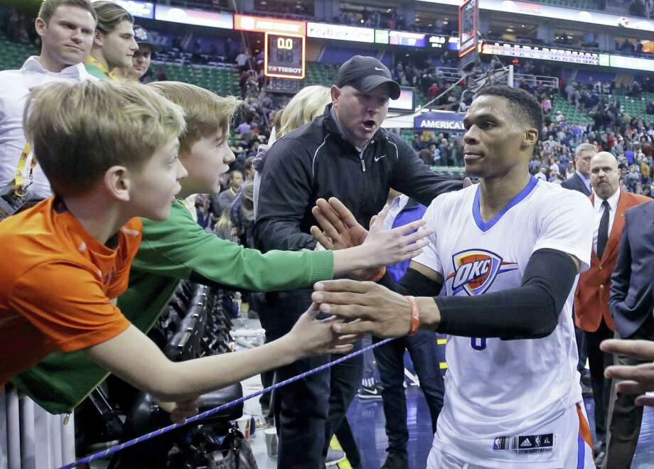 Fans reach for Oklahoma City Thunder guard Russell Westbrook (0) as he leaves the court following a game against the Utah Jazz. Photo: Rick Bowmer — The Associated Press  / Copyright 2017 The Associated Press. All rights reserved.