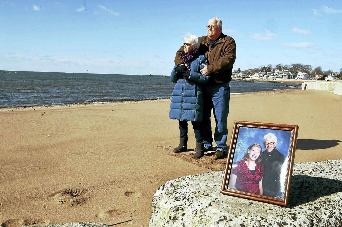 Merry and Douglas Jackson at Silver Sands Beach in East Haven Thursday, March 16, 2016 with a photograph of their daughter Lori with Merry. Lori was killed by her estranged husband in May 2014 who broke into her home and shot her. Merry was also in the home at the time and was also shot four times in the attack.