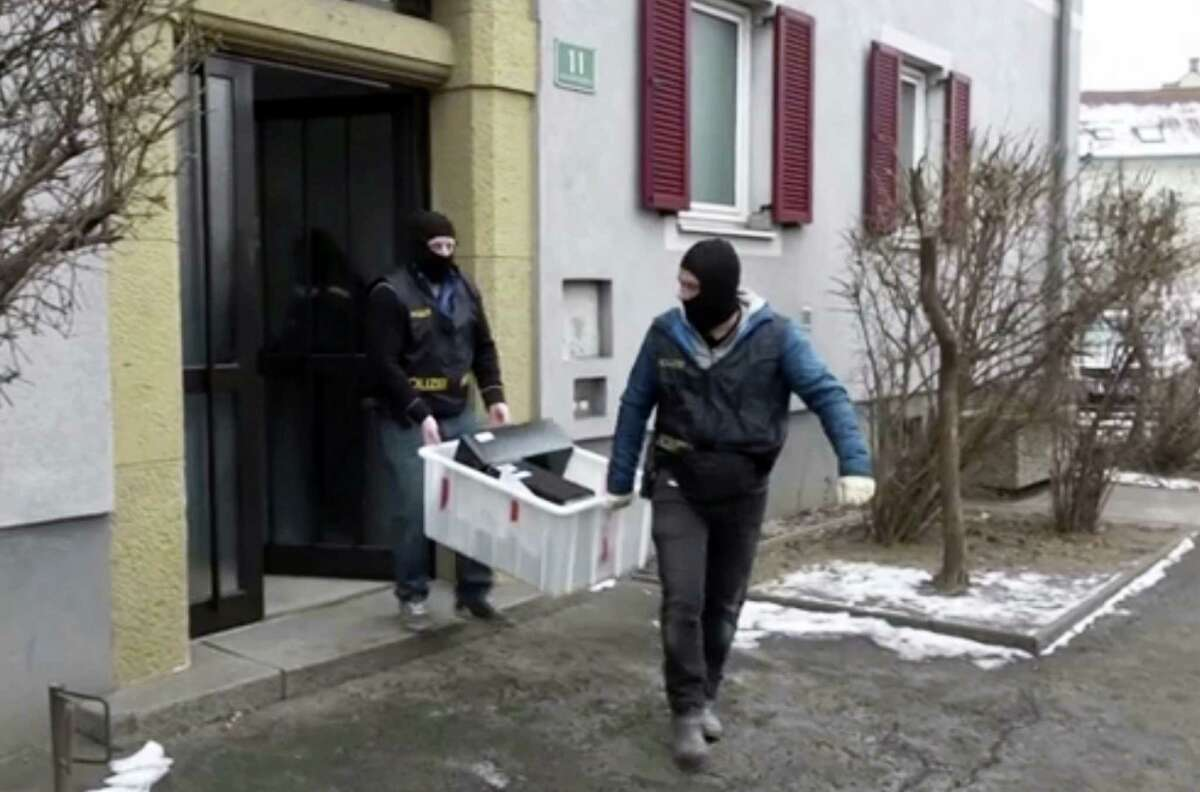 In this image from video masked police officers carry computers out of a house in Graz, Austria, Thursday, Jan. 26, 2017. Austrian police arrested eight suspected terrorists Thursday in a series of early-morning raids in the country's two largest cities that mobilized heavily armed SWAT teams and hundreds of officers supporting them.