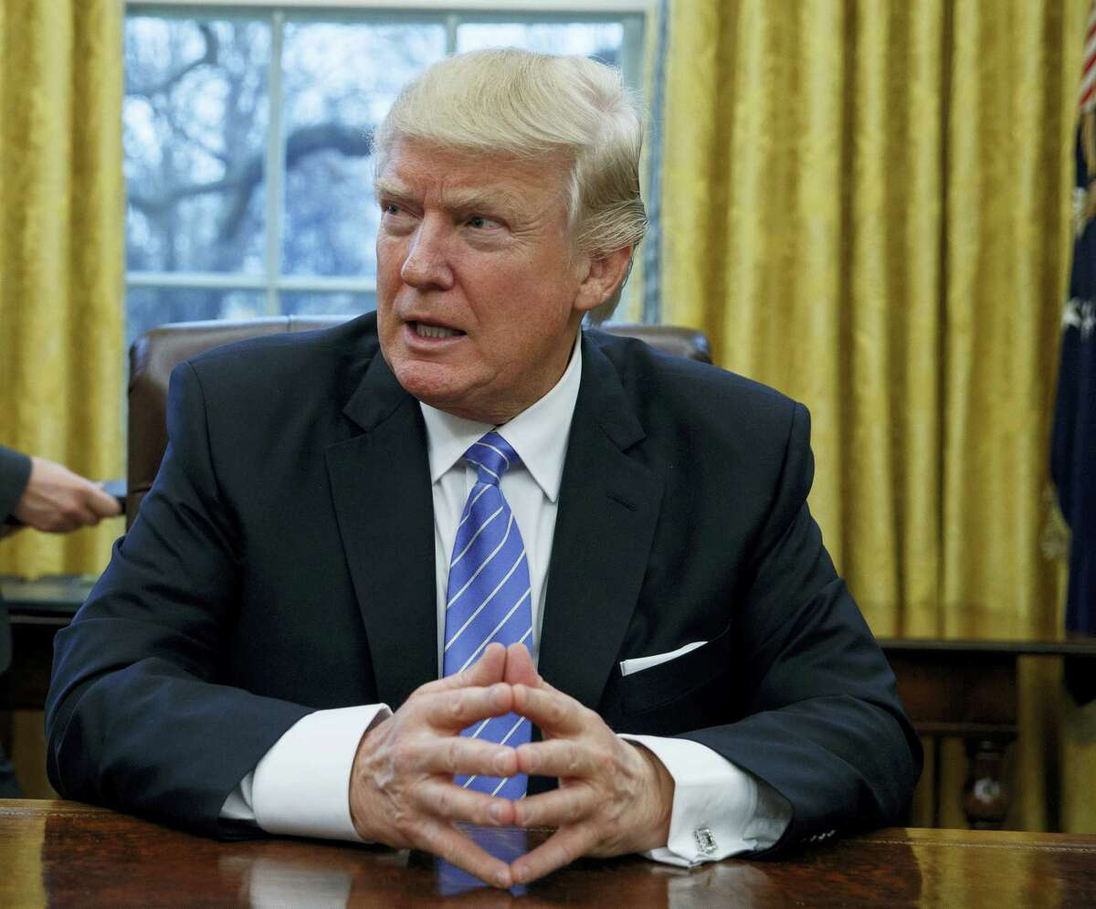 President Donald Trump sits at his desk in the Oval Office of the White House in Washington, Monday, Jan. 23, 2017.