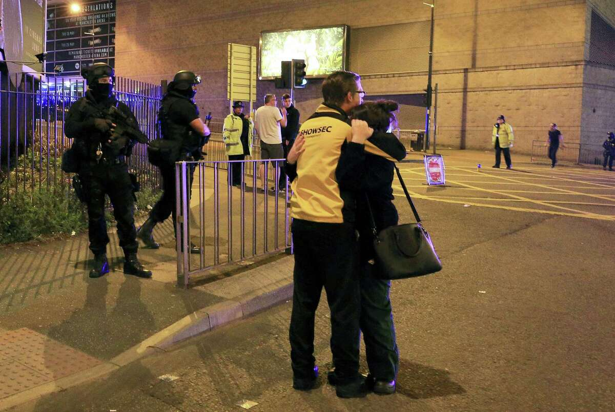 """Armed police stand guard at Manchester Arena after reports of an explosion at the venue during an Ariana Grande gig in Manchester, England Monday, May 22, 2017. Police says there are """"a number of fatalities"""" after reports of an explosion at an Ariana Grande concert in northern England."""