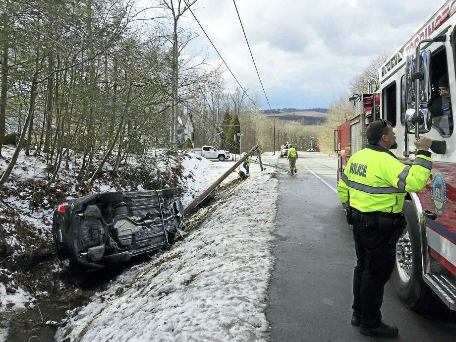 Part of Kennedy Drive was shut down after a vehicle crashed into a utility pole near Fox Run early Thursday afternoon. The driver was flown to Hartford Hospital by Life Star. Above, an officer speaks with a firefighter at the scene. More than 500 customers lost power for several hours. Eversource workers restored power by 3 p.m. Photo: Ben Lambert — The Register Citizen