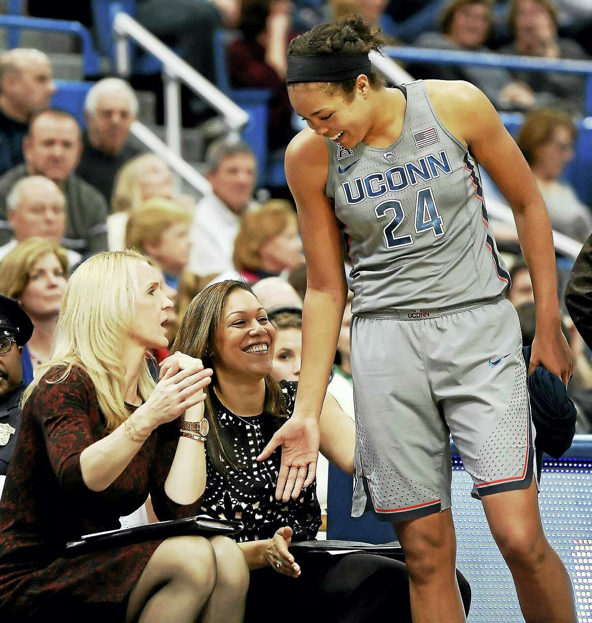UConn assistant coaches Shea Ralph, left, and Marisa Moseley, center, congratulate Napheesa Collier as she comes out of a game earlier this season.