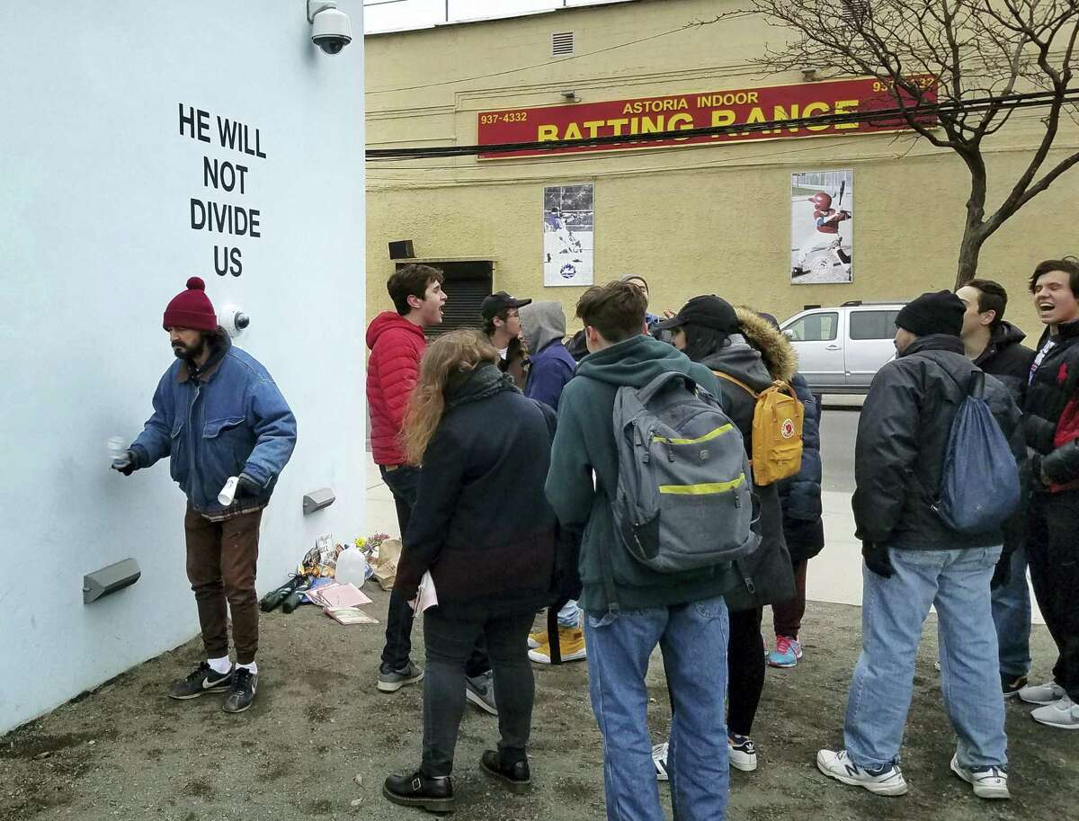 """Actor Shia LeBeouf, left, stands in front of a live-steam camera with the words """"HE WILL NOT DIVIDE US"""" posted on a wall outside of the Museum of the Moving Image as members of the public join LeBeouf in chanting the words """"He will Not Divide Us"""" in the Queens borough of New York. LaBeouf has spent the first four days of the Trump presidency swaying, dancing and chanting, along with anyone who wants to join in. The project by LeBeouf and two other artists opened on Jan. 20 and is expected to go for 4 years, or for """"the duration of the presidency."""""""