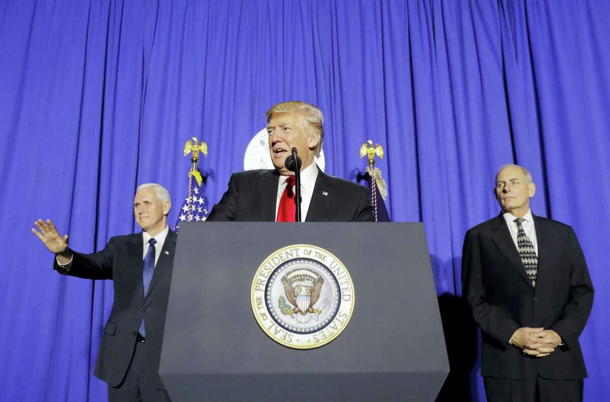 President Donald Trump, accompanied by Vice President Mike Pence, left, and Homeland Security Secretary John F. Kelly, right, speaks at the Homeland Security Department in Washington Wednesday.