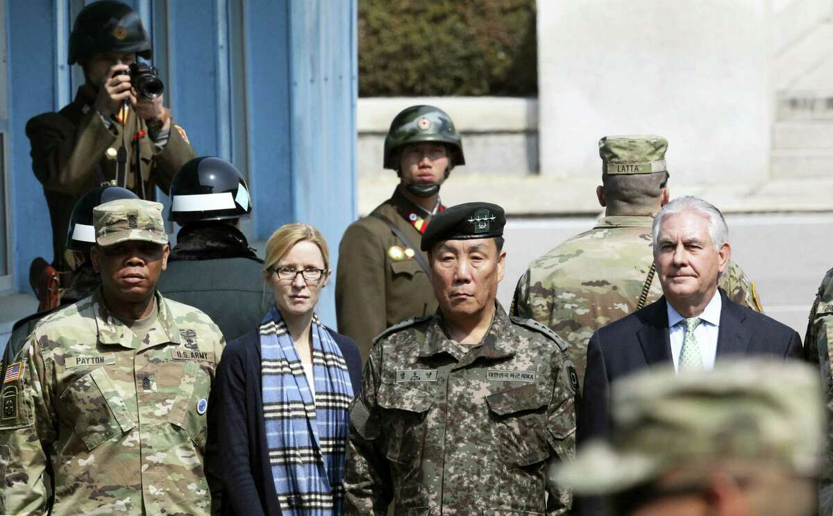 U.S. Secretary of State Rex Tillerson, right, stands with South Korean Deputy Commander of the Combined Force Command Gen. Leem Ho-young, second right, as two North Korean soldiers, top left and top center, look at the south side at the border village of Panmunjom, which has separated the two Koreas since the Korean War, South Korea, Friday, March 17, 2017. Others are: Command Sgt. Maj. Steven L. Payton, left, of the United Nations Command, Combined Forces Command and United States Forces Korea and U.S. Secretary of State's Chief of Staff Margaret Peterlin, second left.