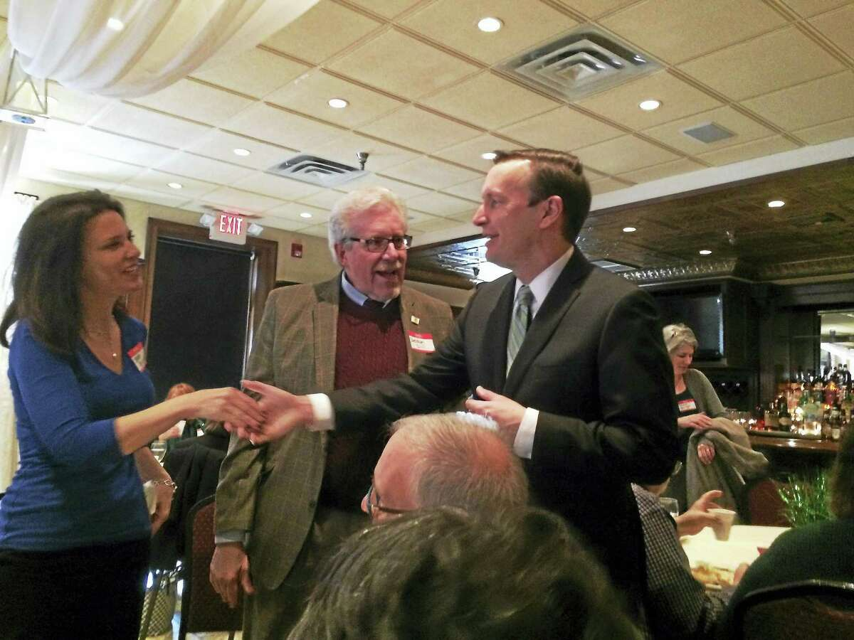 US Senator Chris Murphy, D-Conn., shakes the hand of anunidentified female constituent Friday in Cheshire. Sheldon Dill,president of the Cheshire Chamber of Commerce is shown at center.