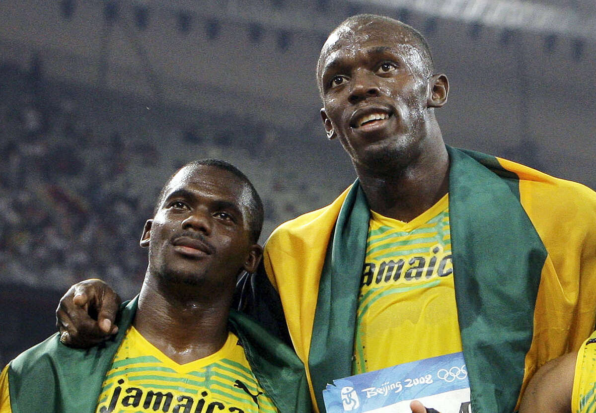 In this Aug. 22, 2008 photo, members of Jamaica's gold medal winning relay team Nesta Carter and Usain Bolt, right, celebrate after the men's 4x100-meter relay final during the athletics competitions in the National Stadium at the Beijing 2008 Olympics in Beijing. Bolt has been stripped of one of his nine Olympic gold medals on Jan. 25, 2017 in a doping case involving teammate Nesta Carter.