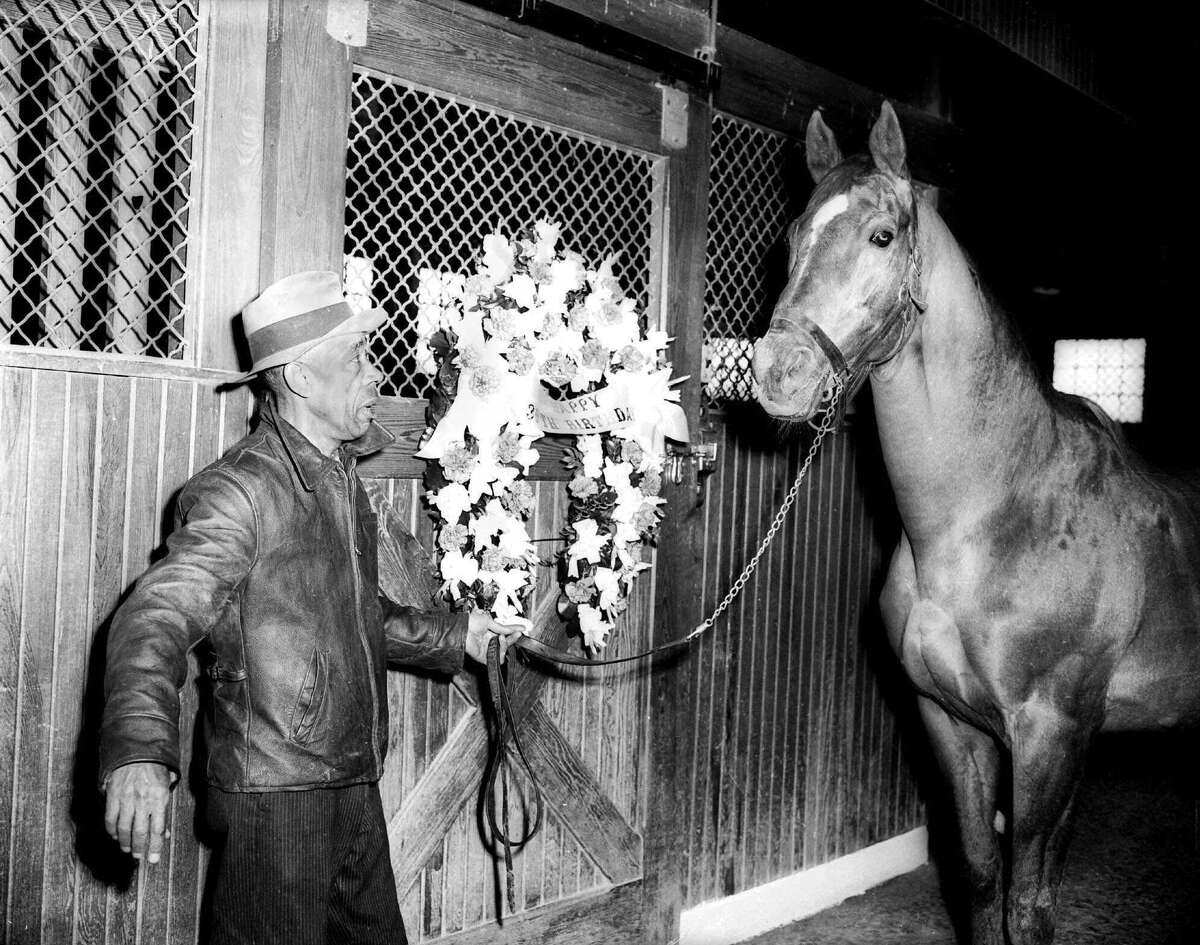 """In this March 30, 1947 photo, Groom Bob Groves leads Man O' War outside the stables near Lexington, Ky. The banner on flowers reads """"Happy Birthday,"""" marking the horse's 30th birthday. The Kentucky Horse Park is planning a year-long celebration to honor the great thoroughbred Man o' War. The Lexington tourist attraction said its plans to open an exhibit March 29, 2017, featuring artifacts from Man o' War's illustrious career as a racehorse and sire. The celebration is part of observances planned for the horse's 100th birthday."""