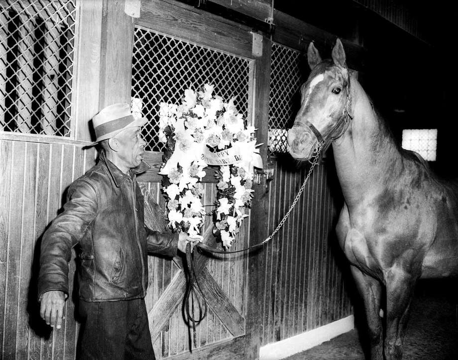 """In this March 30, 1947 photo, Groom Bob Groves leads Man O' War outside the stables near Lexington, Ky. The banner on flowers reads """"Happy Birthday,"""" marking the horse's 30th birthday. The Kentucky Horse Park is planning a year-long celebration to honor the great thoroughbred Man o' War. The Lexington tourist attraction said its plans to open an exhibit March 29, 2017, featuring artifacts from Man o' War's illustrious career as a racehorse and sire. The celebration is part of observances planned for the horse's 100th birthday. Photo: AP Photo/Martin Jessee, File  / AP1947"""