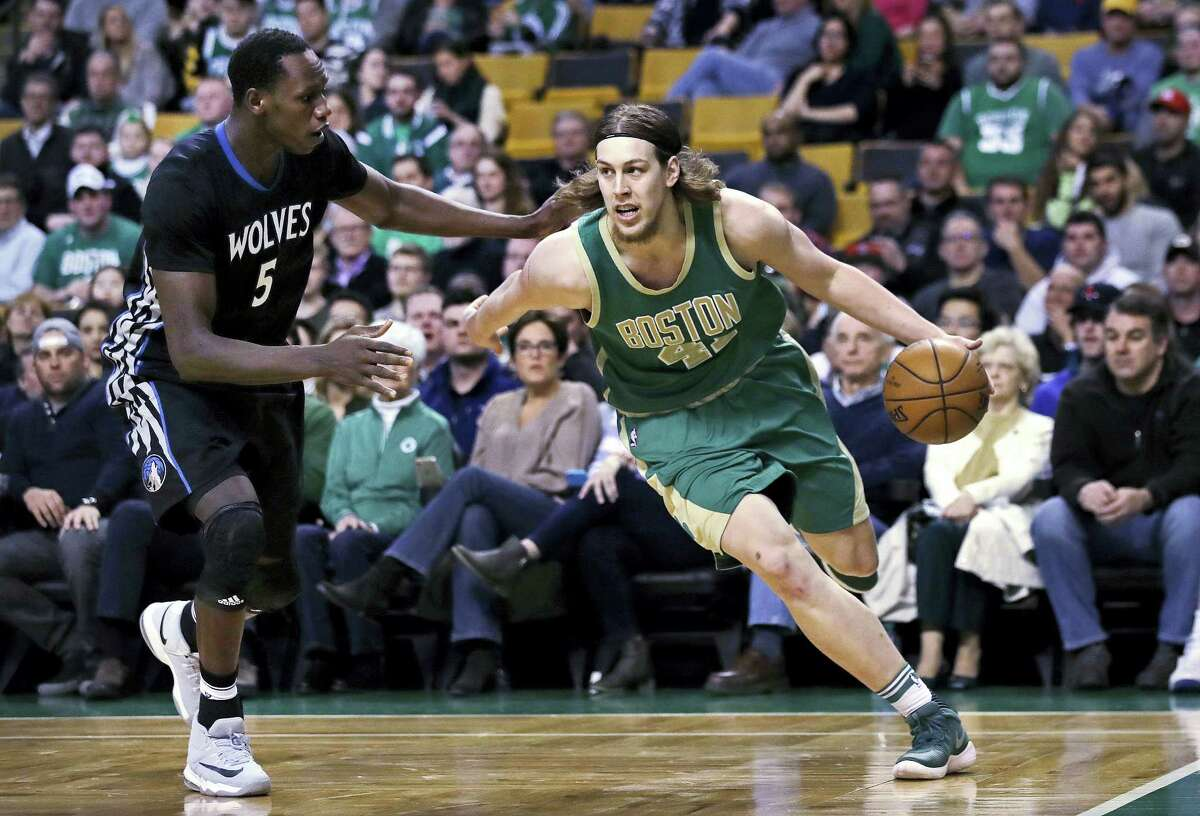 Boston Celtics center Kelly Olynyk (41) drives to the basket against Minnesota Timberwolves forward Gorgui Dieng (5) during the first quarter of an NBA game in Boston, Wednesday, March 15, 2017. (AP Photo/Charles Krupa)