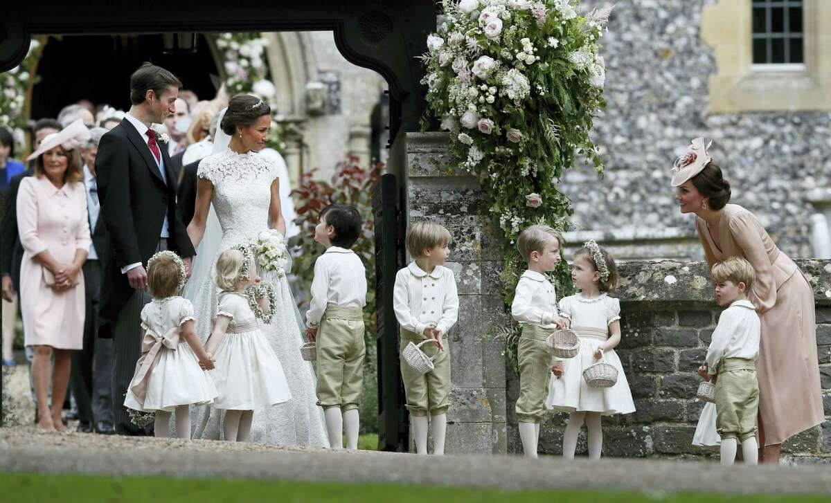 Kate, Duchess of Cambridge, right, stands with her son Prince George as she looks across at Pippa Middleton and James Matthews after their wedding at St Mark's Church in Englefield, England Saturday, May 20, 2017. Middleton, the sister of Kate, Duchess of Cambridge, married hedge fund manager Matthews in a ceremony Saturday where her niece and nephew, Prince George and Princess Charlotte, were in the wedding party, along with sister Kate and Princes Harry and William.