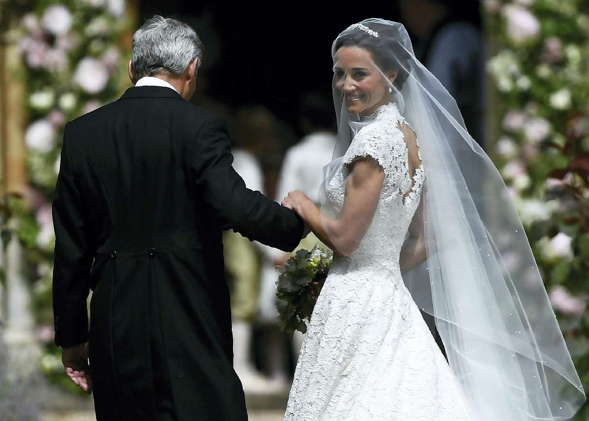 Pippa Middleton, right, is escorted by her father Michael Middleton, as she arrives for her wedding to James Matthews, at St Mark's Church in Englefield, England, Saturday, May 20, 2017.