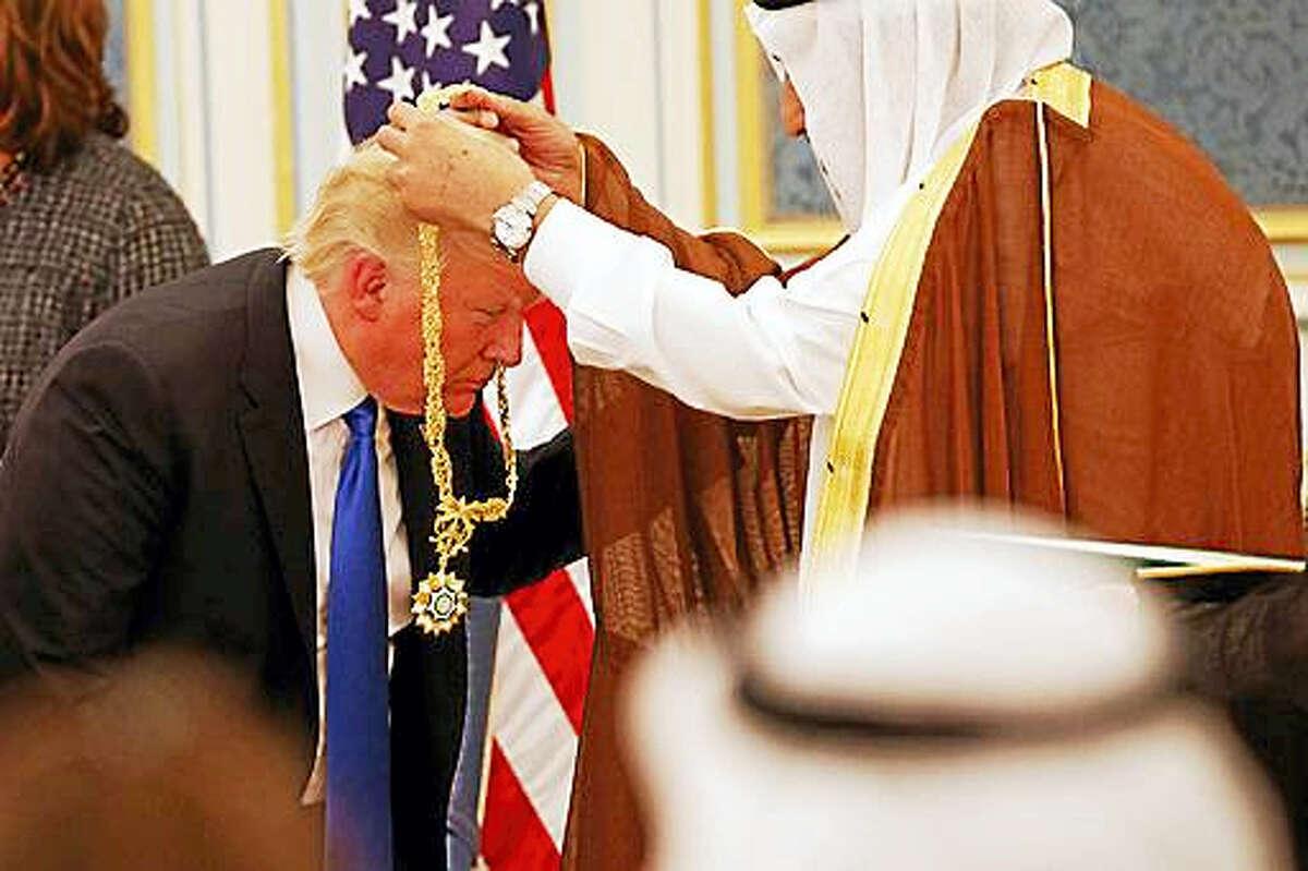 Saudi King Salman presents President Donald Trump with The Collar of Abdulaziz Al Saud Medal at the Royal Court Palace, Saturday, May 20, 2017, in Riyadh.