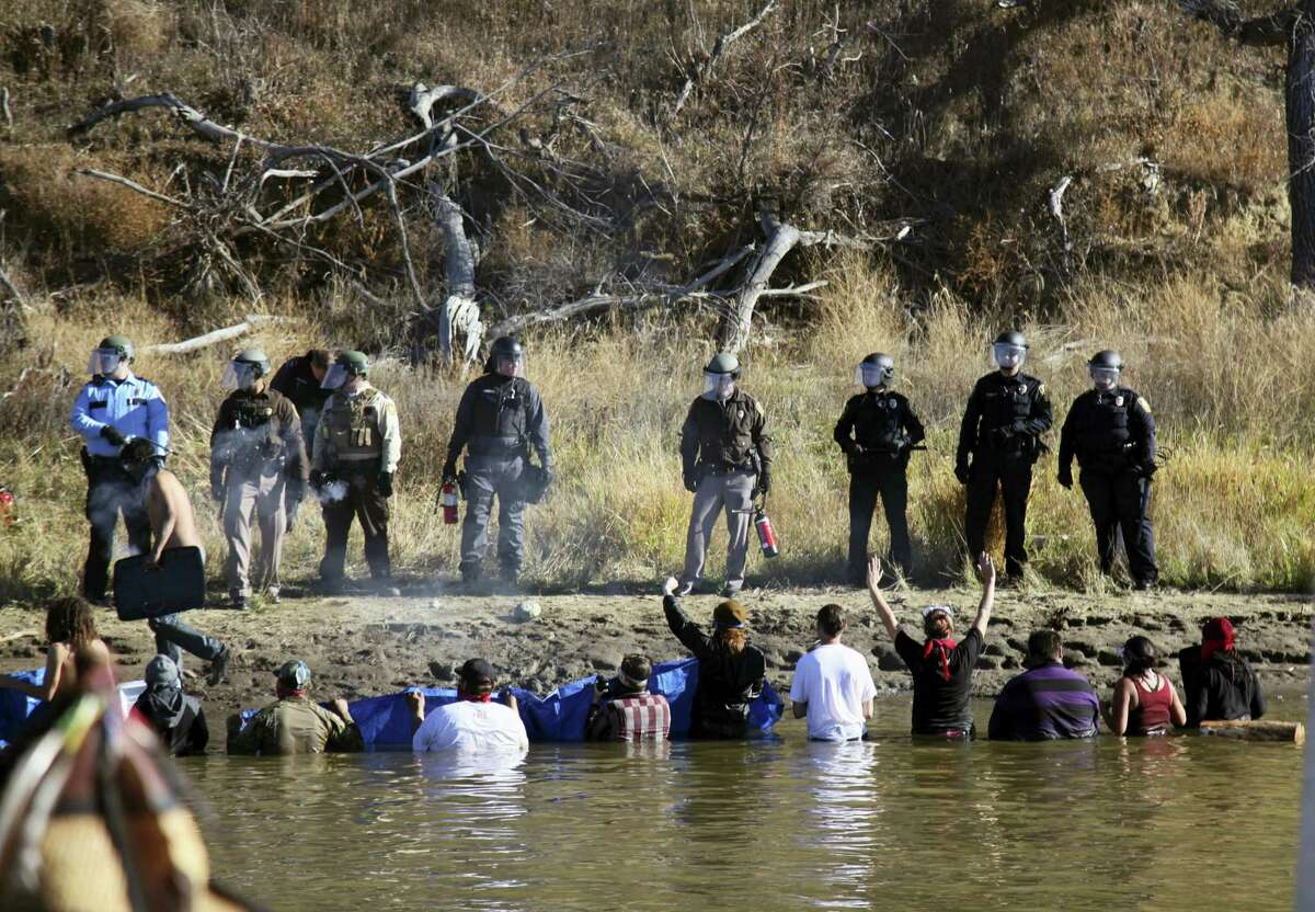 In this Nov. 2, 2016, file photo, protesters demonstrating against the expansion of the Dakota Access pipeline wade in cold creek waters confronting local police near Cannon Ball, N.D. North Dakota officials appear poised to go after the U.S. government — and thus U.S. taxpayers — to recoup more than $38 million in state expenses related to months of protests against the Dakota Access pipeline.