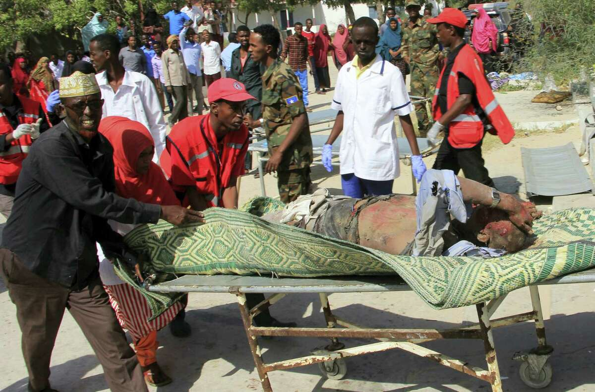 A man who was wounded in a suicide car bomb attack on a hotel is being carried by Somali Red Cross workers and civilians for treatment in Mogadishu, Somalia, Wednesday, Jan 25, 2017. Gunmen from Somalia's violent Islamic extremist rebels fought their way into a hotel in the Somali capital after a suicide car bomb exploded at its gates, a police officer said Wednesday.
