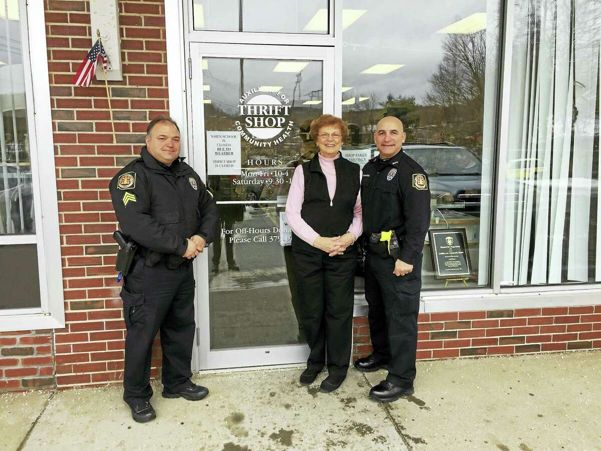 Ben Lambert - The Register Citizen Milly Hudak of the Auxiliary for Community Health and Officers Robert Varasconi and Daniel Pietrafesa of the Winchester Police Department met outside of the auxiliary thrift shop Wednesday to receive a donation from the group for the D.A.R.E. program.
