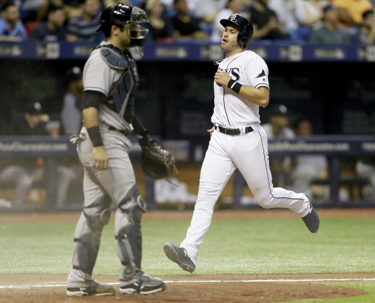 The Rays' Evan Longoria, right, scores in the seventh inning on Friday.