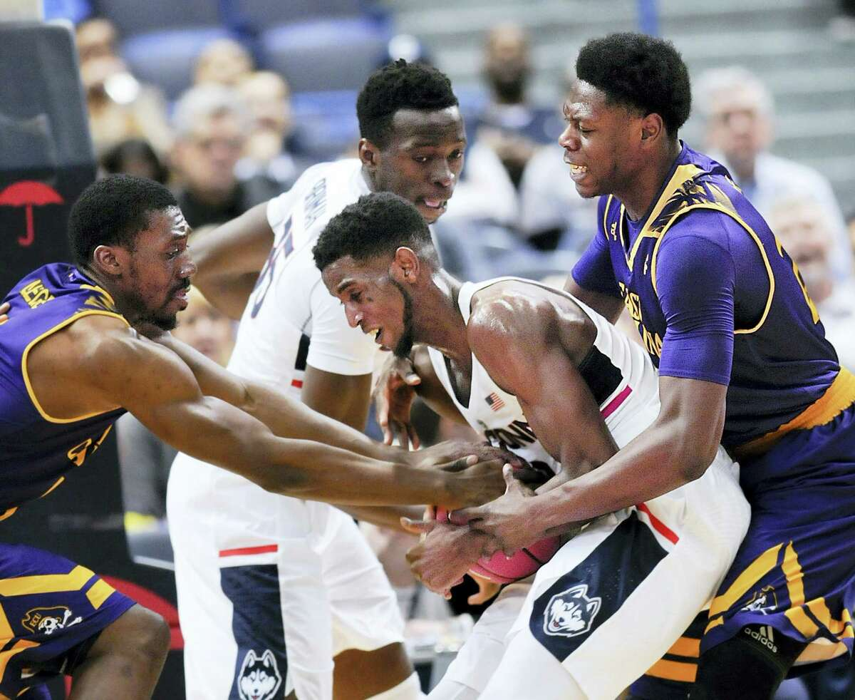 UConn's Kentan Facey (12) hangs on to a rebound against East Carolina defenders in the second half of Sunday's 72-65 win for the Huskies over East Carolina.