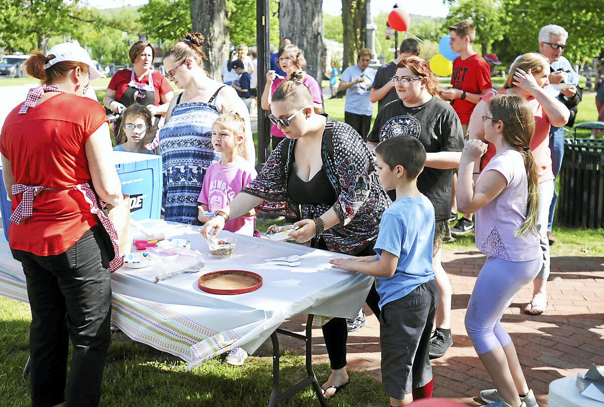 Families line up to get their free ice cream at East End Park in Winsted. The town won a contest for the ice cream party by taking part in a survey, held by the Northwest Hills Council of Governments, which was designed to take in the thoughts of local residents on the future of development in the Northwest Corner.