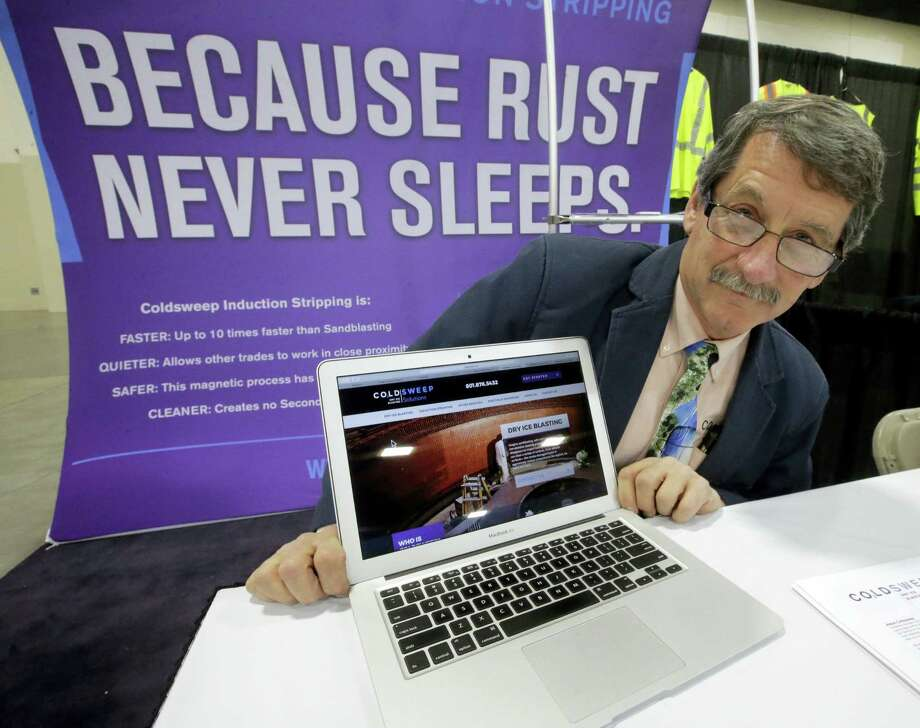 In this Feb. 28, 2017, photo, Randell Heath poses next to a laptop displaying his company's website, in Sandy, Utah. Heath's sandblasting company, near Salt Lake City, had its website hacked and turned into a store selling Viagra and Cialis. Photo: AP Photo — Rick Bowmer  / Copyright 2017 The Associated Press. All rights reserved.