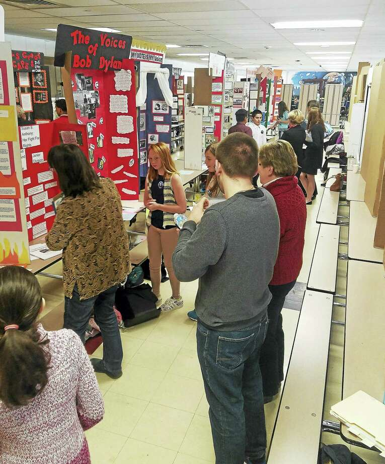 Students, families and faculty look over exhibits at Torrington High School during the history day competition. Photo: Photo By Brian Cofranceso