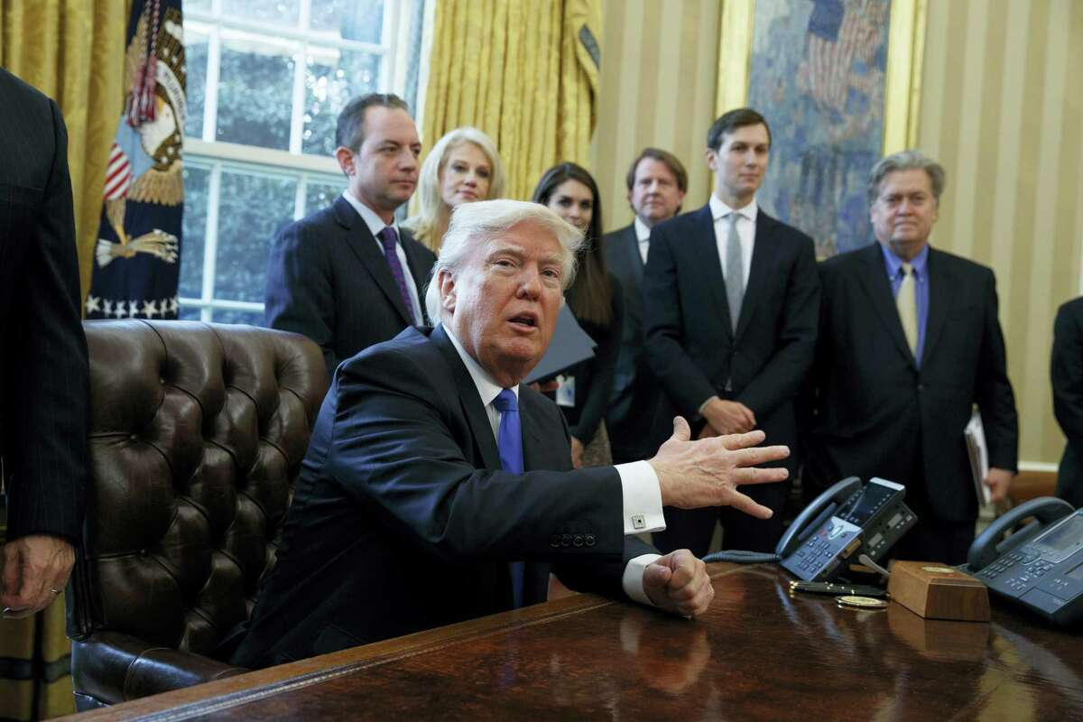 President Donald Trump talks with reporters in the Oval Office of the White House in Washington Tuesday.