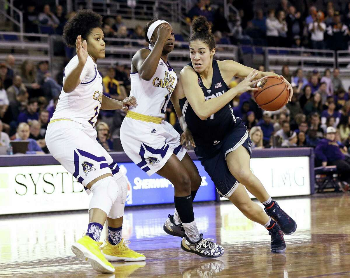 UConn's Kia Nurse drives around East Carolina's Dominique Claytors, left, and Khadidja Toure during the second half of the Huskies' 94th straight victory Tuesday night.