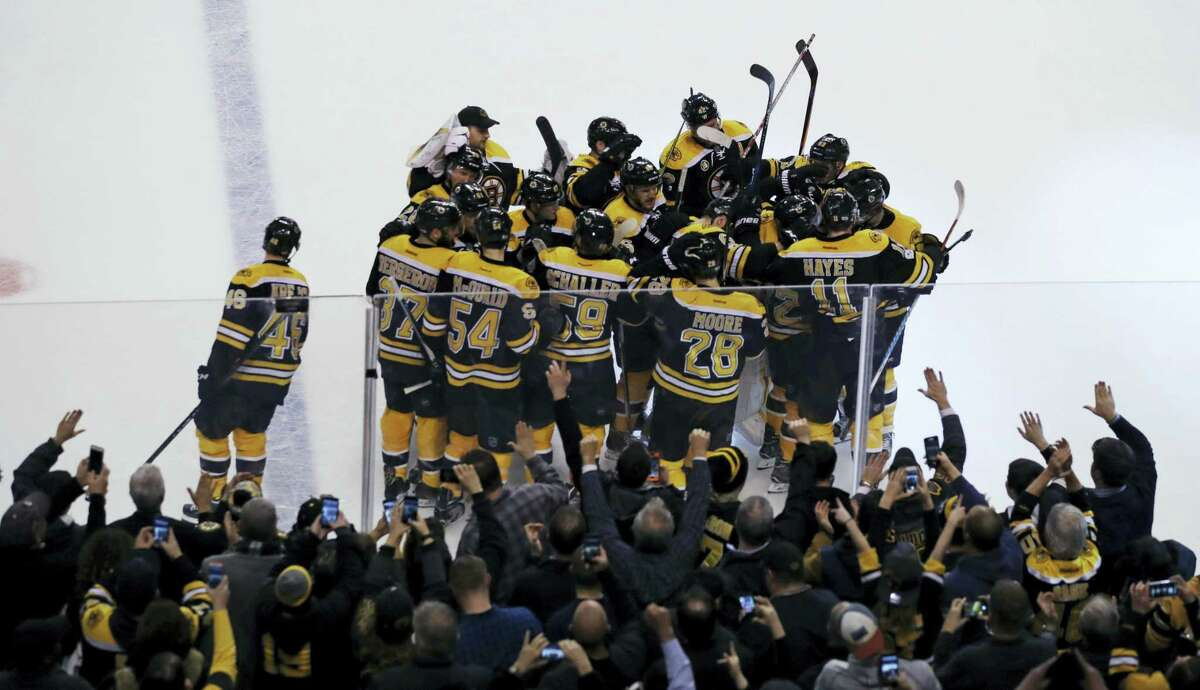 CHARLES KRUPA — THE ASSOCIATED PRESS Fans celebrate as teammates surround Boston Bruins right wing David Pastrnak after his game-winning goal off Detroit Red Wings goalie Jared Coreau during an overtime period Tuesday. The Bruins defeated the Red Wings 4-3.