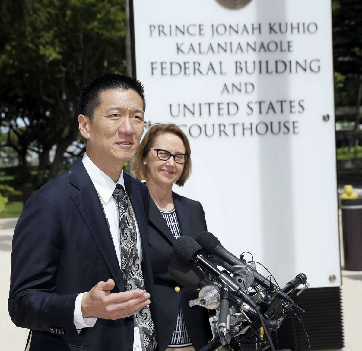 Hawaii Attorney General Douglas Chin, left, and Oregon Attorney General Ellen Rosenblum speak at a press conference outside the federal courthouse, Wednesday, March 15, 2107, in Honolulu. Hearings were scheduled Wednesday in Maryland, Washington state and Hawaii on President Donald Trump's travel ban. The lawsuit claims the ban harms Hawaii by highlighting the state's dependence on international travelers, its ethnic diversity and its welcoming reputation as the Aloha State.