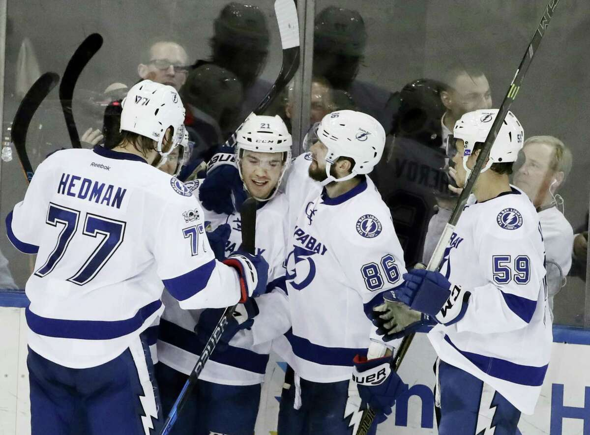 Tampa Bay Lightning's Brayden Point (21) celebrates with teammates Victor Hedman (77), Nikita Kucherov (86) and Jake Dotchin (59) after scoring a goal during the third period of an NHL hockey game against the New York Rangers Monday, March 13, 2017, in New York. The Lightning won 3-2.