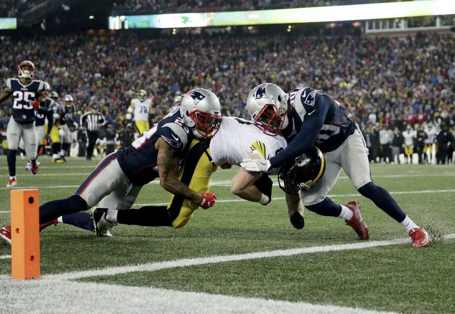 Steelers tight end Jesse James is tackled short of the goal line by Patriots safety Patrick Chung, left, and defensive back Duron Harmon during the AFC championship game on Sunday. Photo: Matt Slocum — The Associated Press  / Copyright 2017 The Associated Press. All rights reserved.