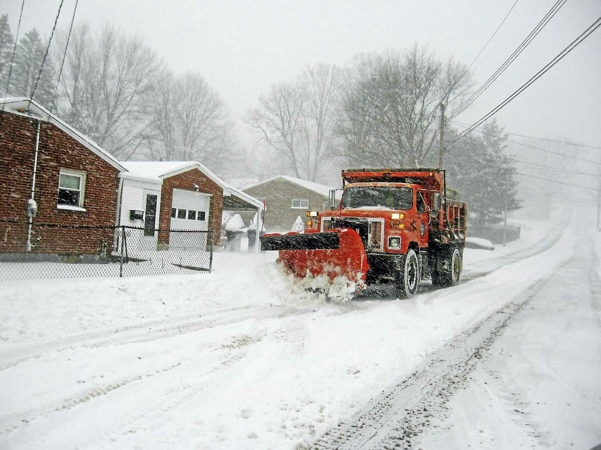 A city plow heads into town, clearing the snow as it goes.