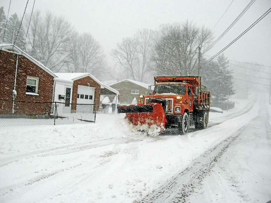 A city plow heads into town, clearing the snow as it goes. Photo: Photo By John Torsiello