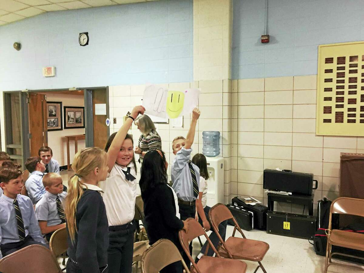 Ben Lambert — The Register Citizen St. Anthony School students cheer for their classmates during the annual geography bee Monday in Winsted.