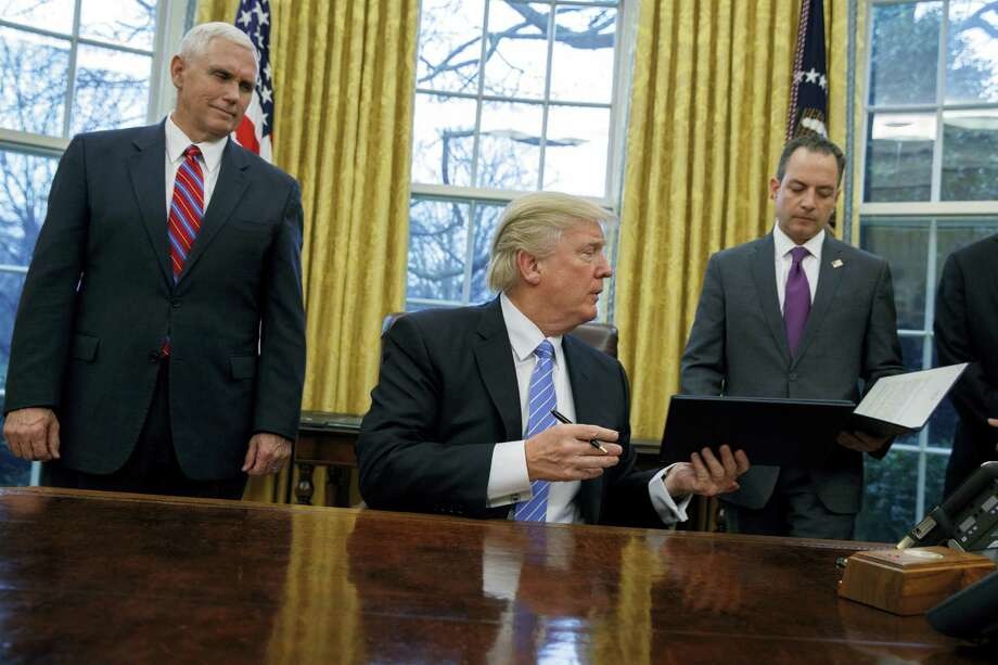 Vice President Mike Pence, left, and White House Chief of Staff Reince Priebus watch as President Donald Trump hands over an executive order to withdraw the U.S. from the 12-nation Trans-Pacific Partnership trade pact agreed to under the Obama administration on Jan. 23, 2017 in the Oval Office of the White House in Washington. Photo: AP Photo/Evan Vucci  / Copyright 2017 The Associated Press. All rights reserved.