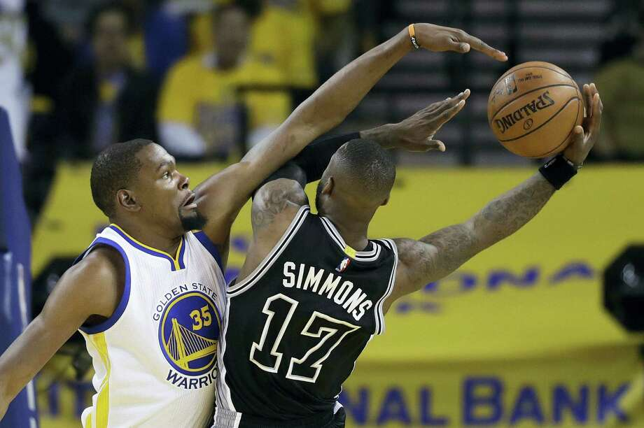 San Antonio Spurs' Jonathon Simmons (17) drives to the basket as Golden State Warriors' Kevin Durant (35) defends during the first half of Game 2 of the NBA basketball Western Conference finals, Tuesday, May 16, 2017, in Oakland, Calif. The Warriors won 136-100. Photo: JOSE SANCHEZ — THE ASSOCIATED PRESS  / Copyright 2017 The Associated Press. All rights reserved.
