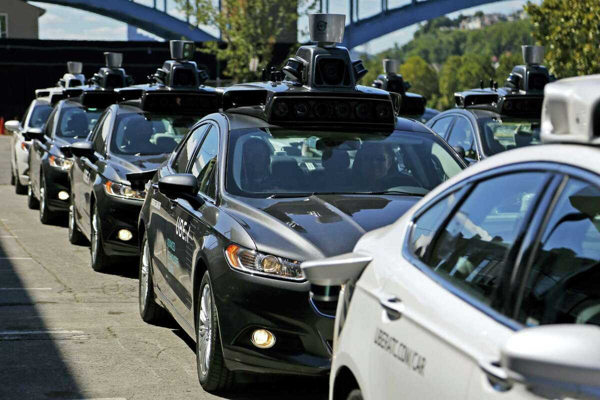 FILE - In this Monday, Sept. 12, 2016, file photo, a group of self-driving Uber vehicles position themselves to take journalists on rides during a media preview at Uber's Advanced Technologies Center in Pittsburgh. U.S. President Donald Trump's economic plans are nothing if not ambitious, including his vision of creating 25 million jobs over 10 years. However, the widespread use of robots and automation by companies has increasingly allowed businesses to operate with fewer workers. For example, Uber is experimenting with self-driving cars, and restaurant chains like Eatsa can now serve lunch and dinner through an automated order-and-payment system, and no cashiers or servers are necessary. (AP Photo/Gene J. Puskar, File)