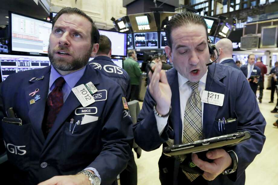 Specialist Michael Pistillo, left, and trader Tommy Kalikas work on the floor of the New York Stock Exchange Monday. Photo: Richard Drew — The Associated Press  / AP