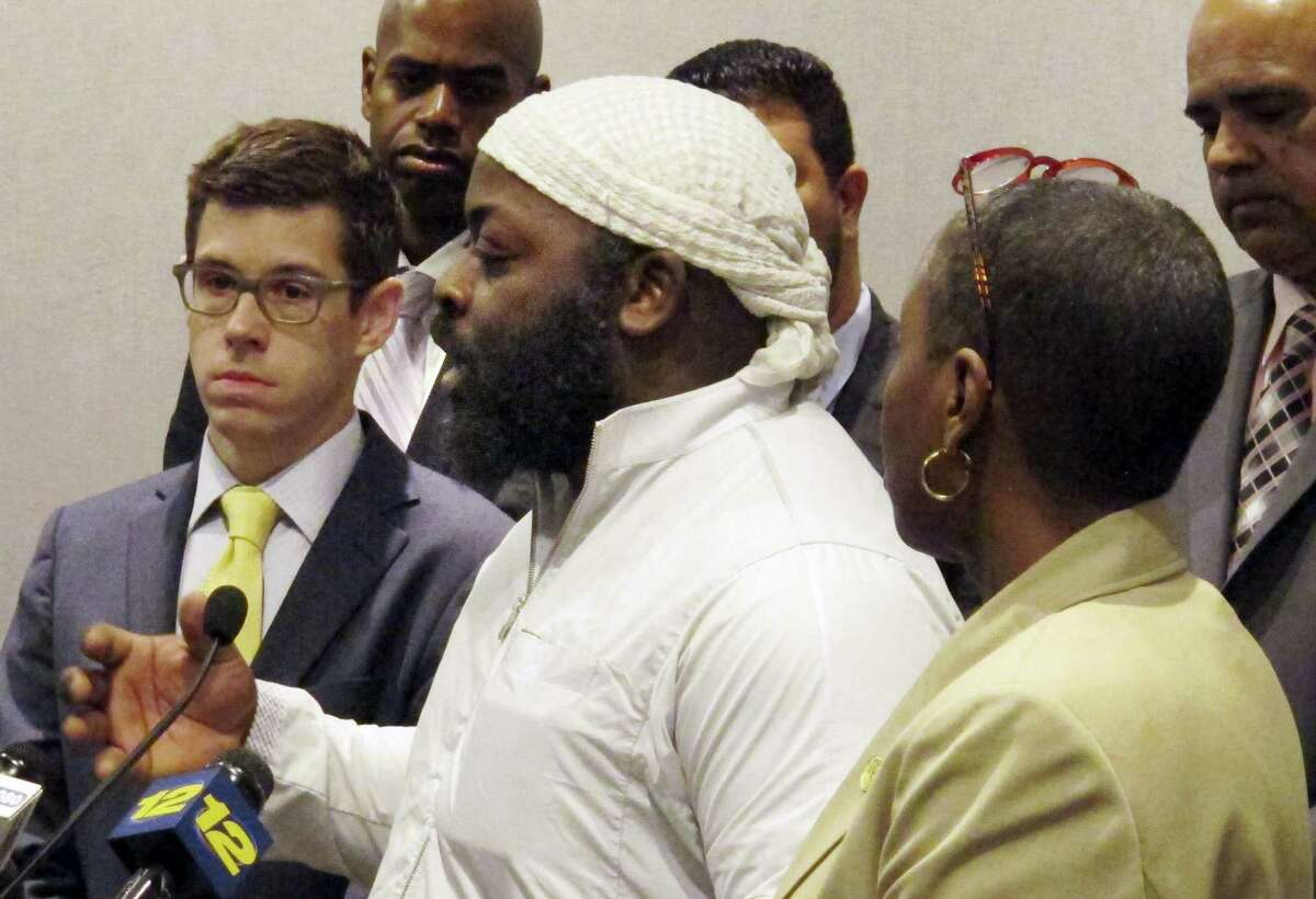 Isa Mujahid, center, of CTCORE-Organize Now!, speaks during a news conference at the Legislative Office Building May 16, 2017 in Hartford, Conn. Beside him are David McGuire, left, executive director of the American Civil Liberties Union of Connecticut, and state Rep. Robyn Porter, right, of New Haven. The group urged the legislature to pass a bill aimed at improving investigations of shootings involving police after an officer shot and killed an unarmed 15-year-old boy who was driving a stolen car in Bridgeport last week.