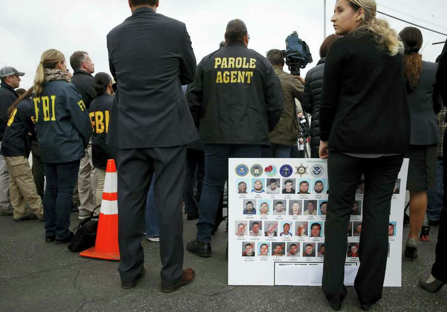 An FBI employee, who declined to give her name, holds a board showing images of MS-13 gang members during a news conference Wednesday, May 17, 2017, in Los Angeles. Nearly two dozen members and associates of MS-13 were arrested Wednesday morning as hundreds of federal and local law enforcement fanned out across Los Angeles, serving arrest and search warrants. Photo: AP Photo/Jae C. Hong   / Copyright 2017 The Associated Press. All rights reserved.
