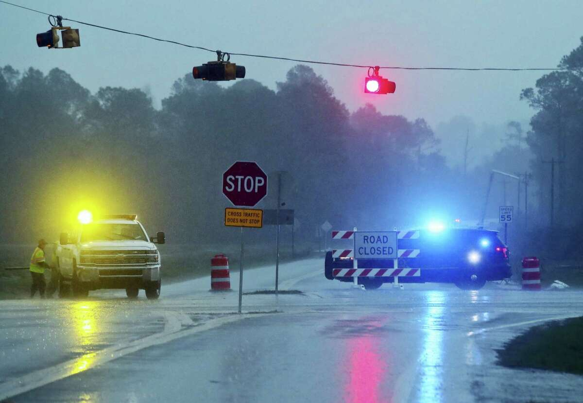 """A Brooks County Sheriff and officials block Highway 122 as power line workers repair a downed pole in the background on Jan. 22, 2017 near Barney, Ga. The National Weather Service said Sunday that southern Georgia, northern Florida and the corner of southeastern Alabama could face """"intense and long track"""" tornadoes, scattered damaging winds and large hail."""