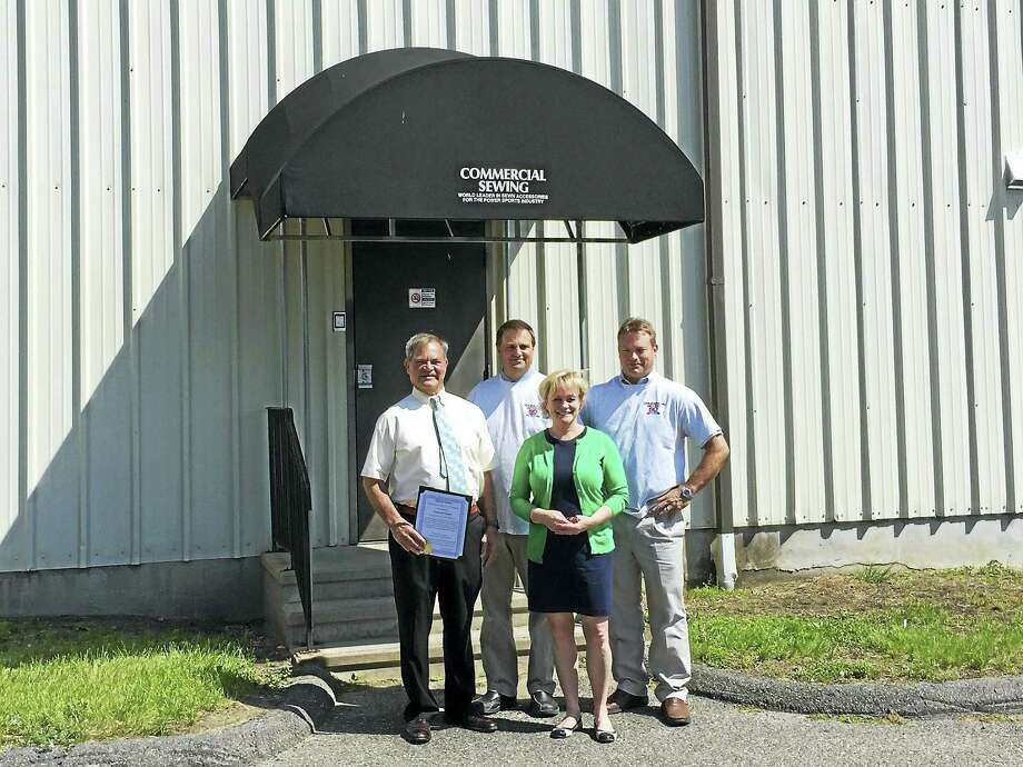 The employees of Commercial Sewing celebrated the company's 50th anniversary Wednesday in Torrington. Above, from left, are founder Sam Mazzarelli, son Stephen Mazzarelli, Mayor Elinor Carbone, and son David Mazzarelli. Photo: Ben Lambert — The Register Citizen