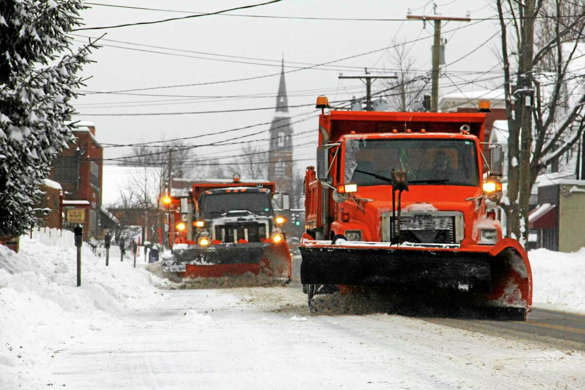 City plows head down Main Street in Torrington during a 2014 storm. A blizzard is expected to hit the state Tuesday.